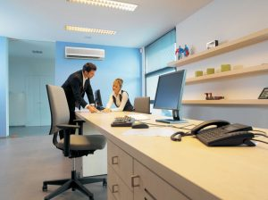 Young business woman & men in discussion in office