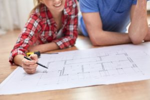Happy couple look at blueprints for their new home