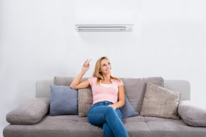 A young woman smiles relaxing on a sofa under her air conditioner