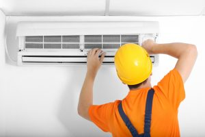 A technician repairs a wall mounted air conditioning unit