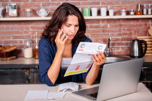 Woman sits at laptop on the phone in her kitchen looking unhappy about energy bills