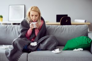 A young sick woman sits on couch suffering from allergies